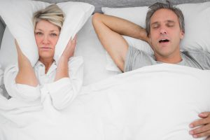 Couple in bed, man snoring